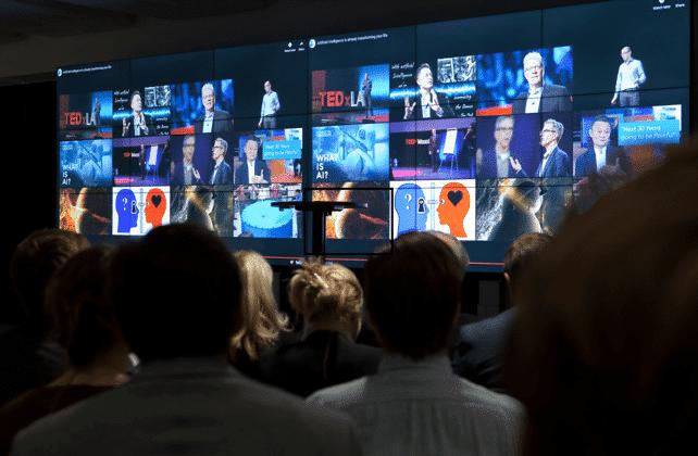 Flertalet personer tittar på vägg med flera skärmbilder i samlad vy