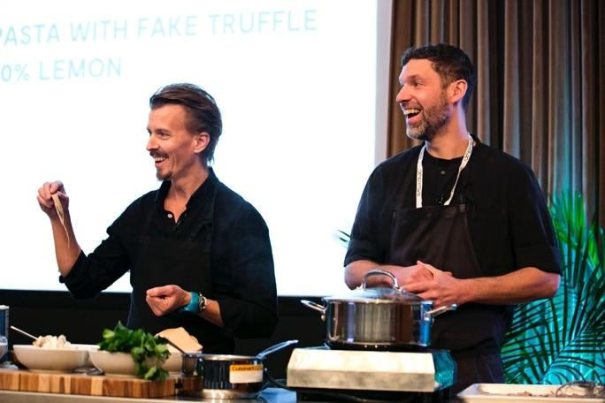 två personer lagar mat framför publik