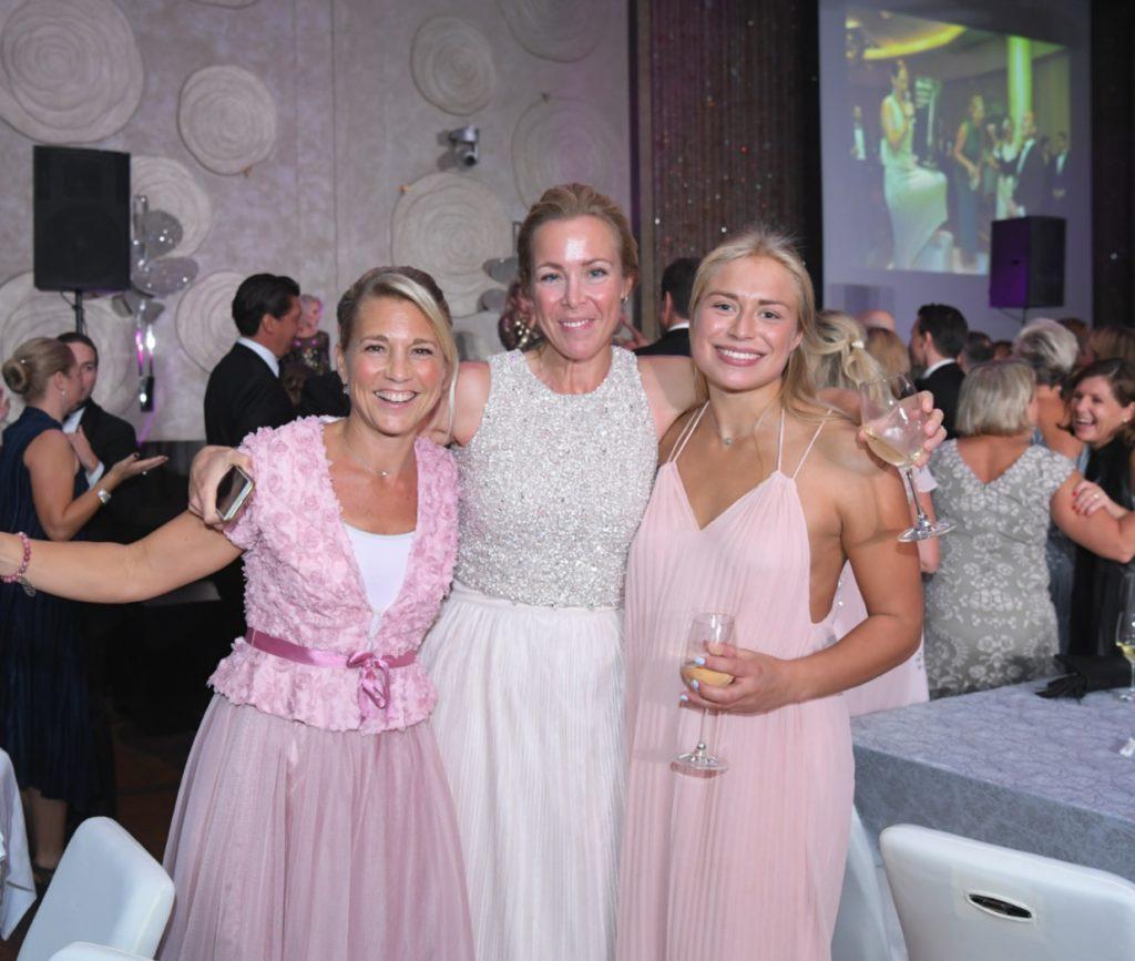 Tre tjejer i festkläder med övriga deltagare bakom.