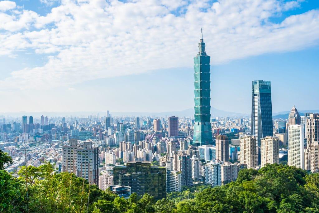 Stadsvy över Taipei City. Två höghus sticker upp ovanför övriga höghus en ljus sommardag med grönska i förgrunden.