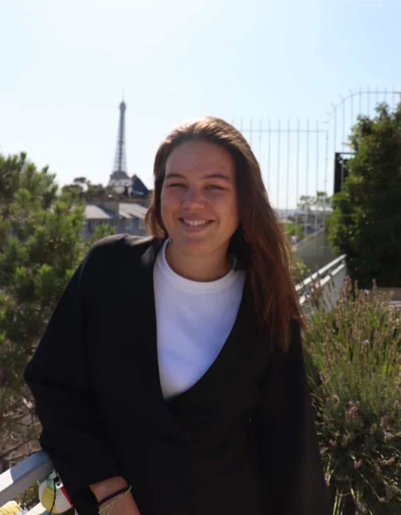 Bild på Inès, och Eiffeltornet i bakgrunden. Hon har mörk tröja och brunt hår.