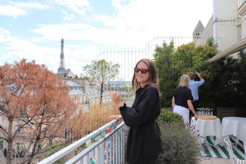 Inès står utomhus på en terass med Eiffeltornet i bakgrunden. Hon har mörk jacka, solglasögon och brunt hår.