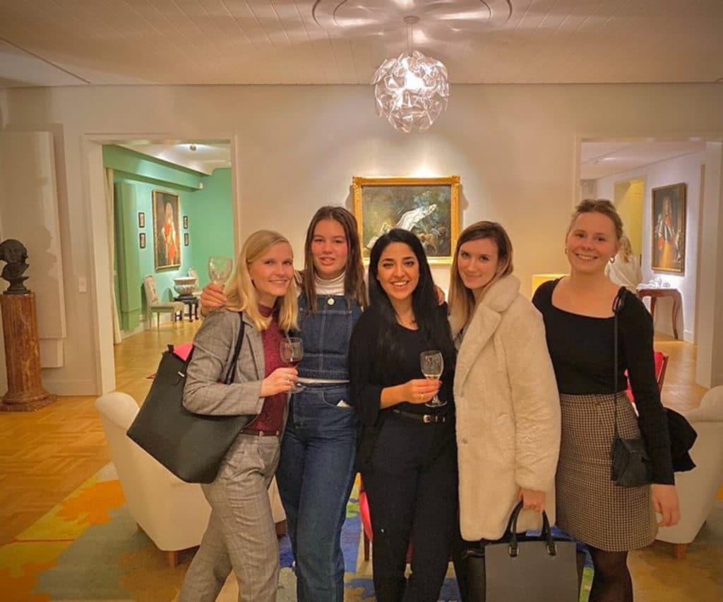 Inès och fyra tjejer står i en stor lokal klassiskt inredd med konst i bakgrunden.