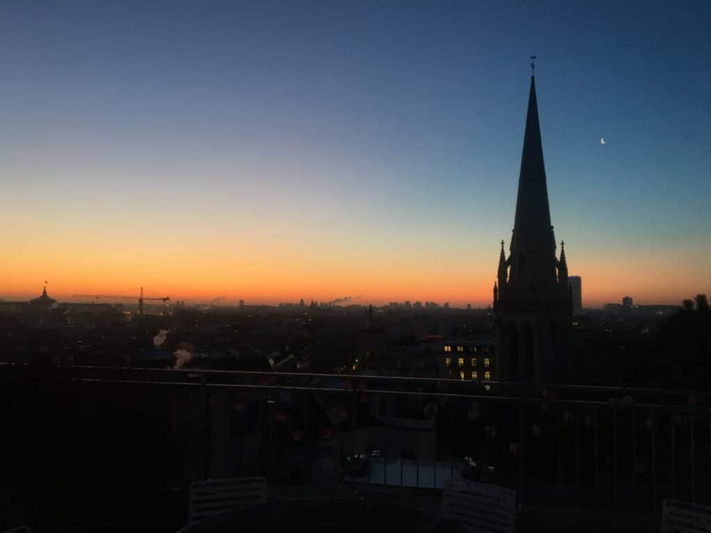Översiktsvy över Paris, solen ligger lågt och husen syns bara som konturer.