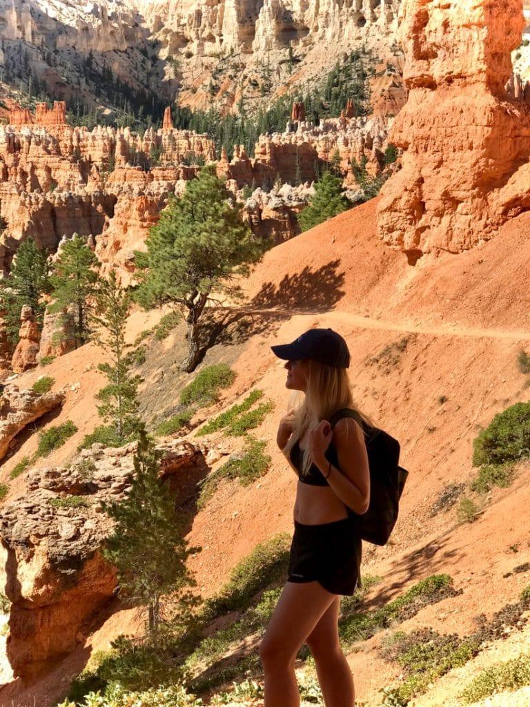Alicia Juhlin vandrar i bergigt område i varmt väder. Hon bär ryggsäck, shorts och svart topp samt svart keps.