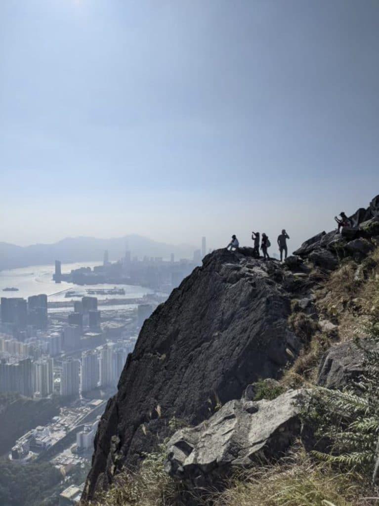 Vy över staden Hong Kong från ett klippblock högt uppe. Husen syns bakom ett tunt dis.