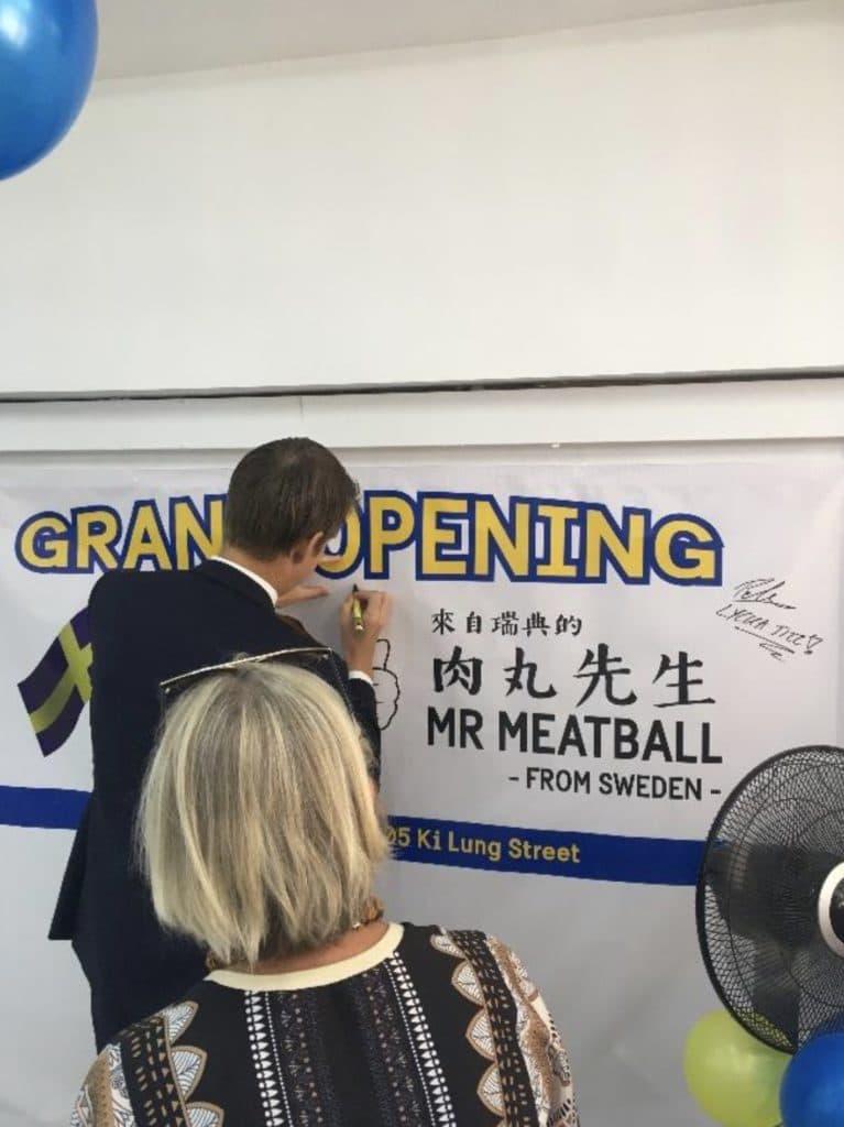 Ryggtavla på en manlig person som skriver på en väggaffisch med åskådare i förgrunden.