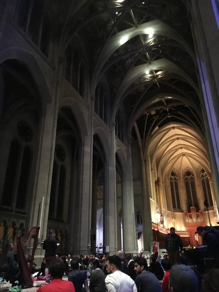 Inifrån en katedral, Grace Cathedral. Högt i tak och mörkt belyst, människor i nederkanten på bilden som besöker.