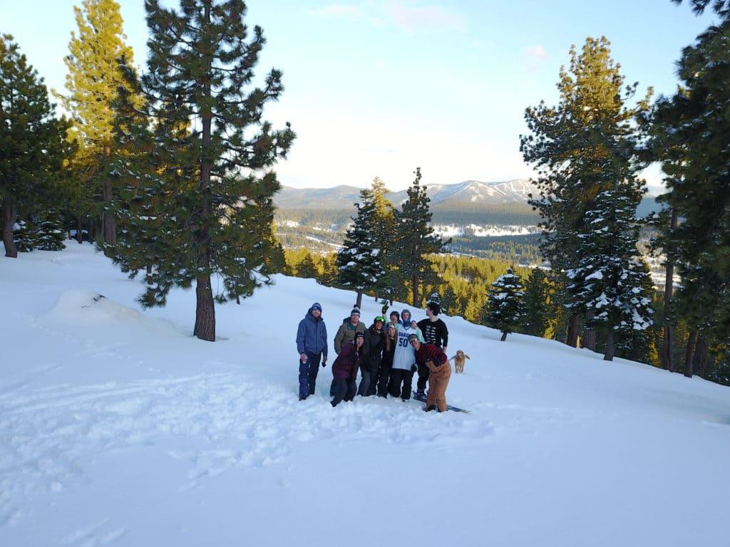 Nio personer står i snön i sluttande landskap med träd runtomkring och utsikt över berg.