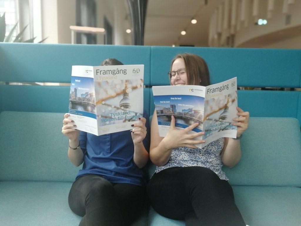 Två tjejer sitter i en turkos soffa och håller varsitt tidningsuppslag framför sig