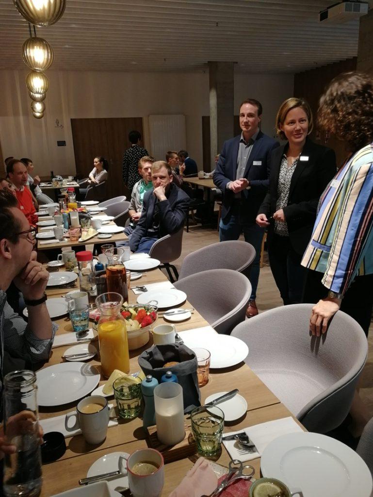 Cirka 15 personer i matsalsmiljö. Tre personer står och pratar med varandra. Belysningen är dämpad.