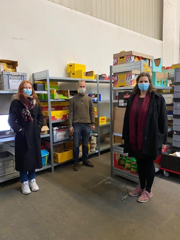 Tre personer står i en lagerlokal omgiven av snacks, chips och liknande matvaror. En kille och två tjejer. Alla tre har munskydd.