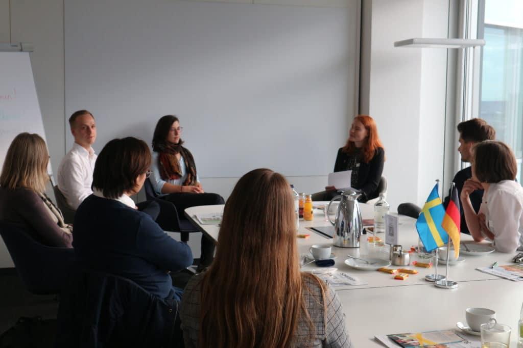 Åtta personer i möte runt ett konferensbord.