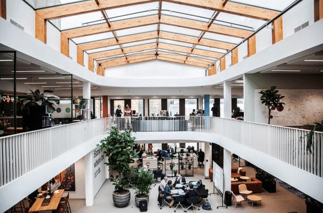 Interiörbild från övervåning där man har utsikt ned mot undervåningen. Öppen planlösning, interiör i ljust trä och vita väggar. Människor sitter och står i olika grupperingar.