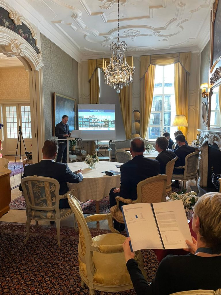 Ett antal personr sitter inne i en elegant inredd lokal och lyssnar på en föreläsning med bilder på en projektor