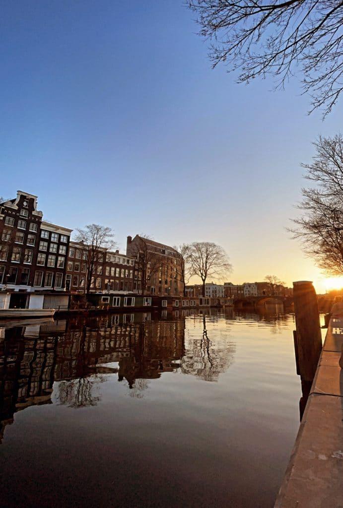 Vy ut över en kanal kvällstid. Blå himmel, solnedgång