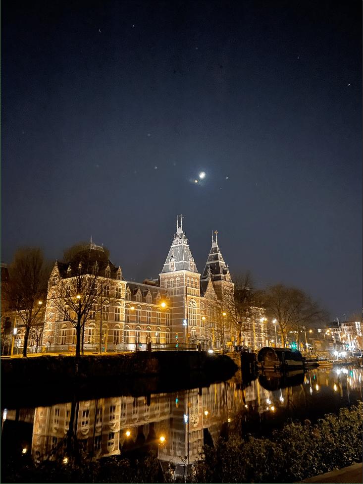 Palatsliknande byggnad på kväll upplyst av gatlyktor och externa lampor