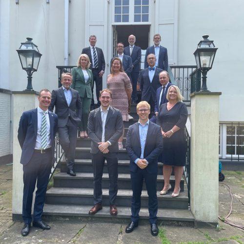 13 personer propert klädda står i en trapp upp till ett elegant äldre hus
