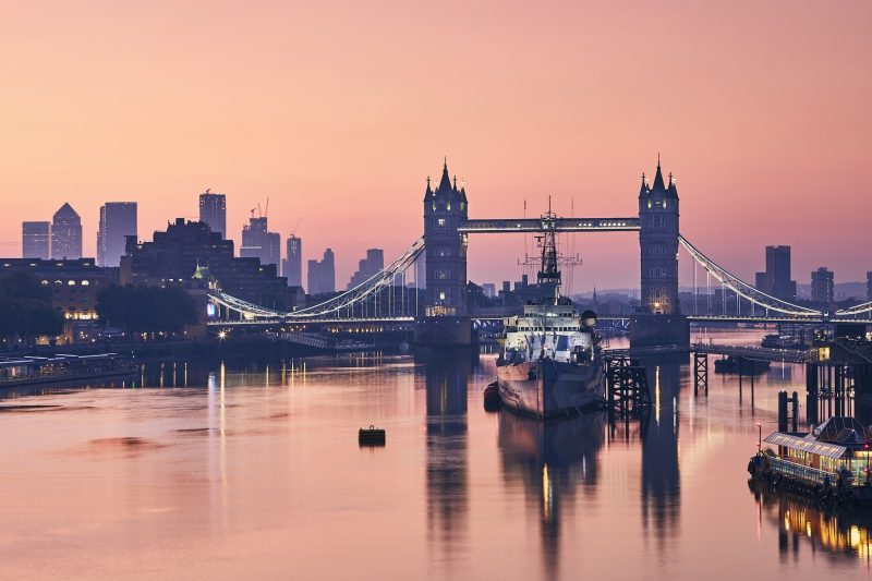 Skyline över london och Tower Bridge. En bro i bakgrunden av vatten på kvällen.